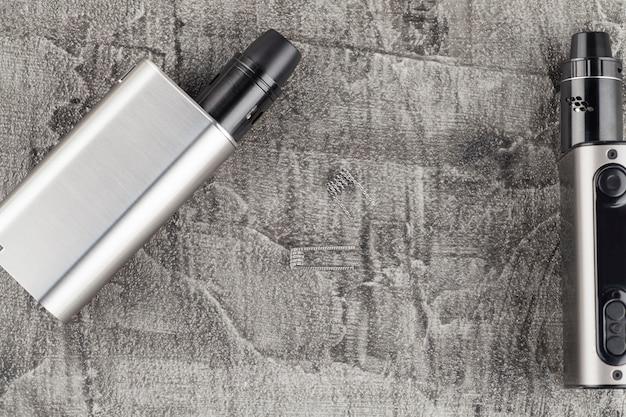 Moderne elektronische sigaret op een concrete achtergrond.