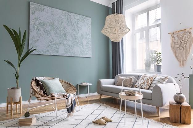 Moderne en bohemien compositie van interieur met grijze bank, rotan fauteuil, houten kubus, geruit kussen, tropische planten, kleine tafel en elegante accessoires