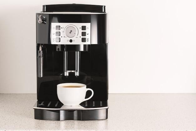 Moderne espressomachine met een kopje in de keuken