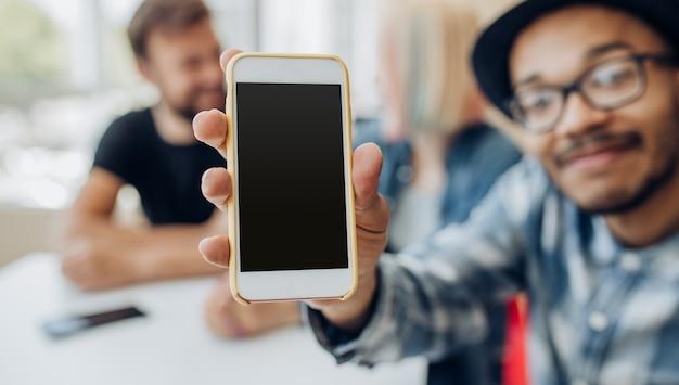 Moderne etnische man met mobiele telefoon met zwart scherm
