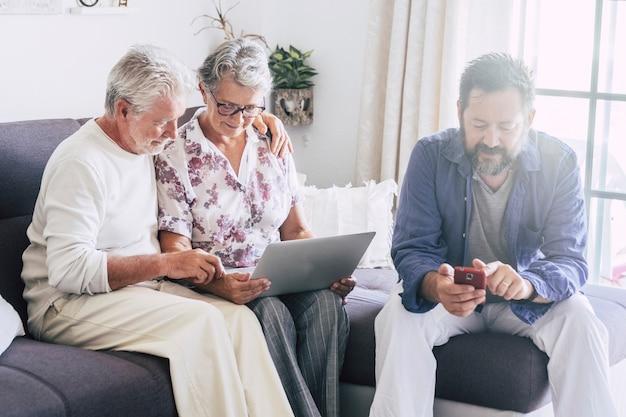 Moderne familie thuis zittend en met behulp van technologie