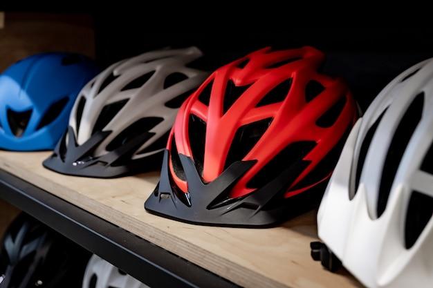 Moderne fietshelmen voor familie of groep mensen. fietsen en verkeersveiligheidsconcept - veelkleurige stijlvolle helmen die op een rij liggen