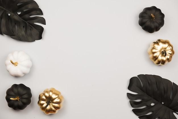 Moderne flat lag met zwarte en gouden halloween-pompoen