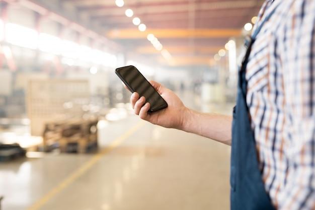Moderne gadget met touchscreen gehouden door jonge ingenieur of technicus in werkkleding sms'en per werkplek