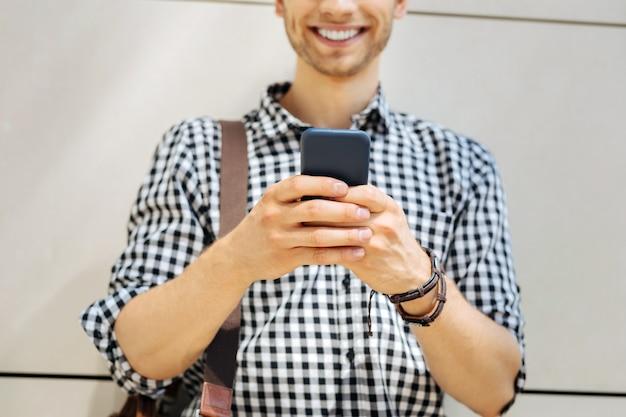 Moderne gadget. selectieve aandacht van een mobiele telefoon die in handen is van een slimme jongeman