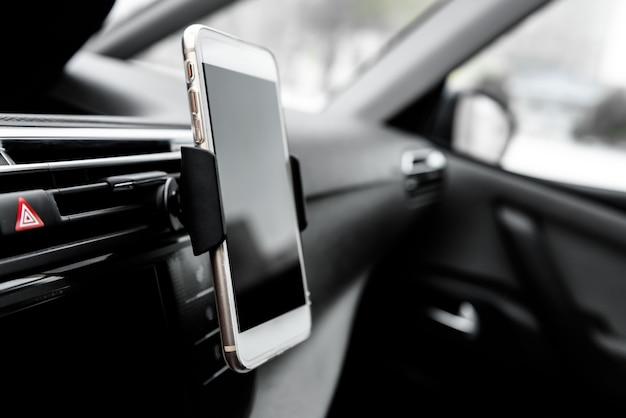 Moderne gadget voor smartphoneapparaten gemonteerd op telefoonhouder op autodashboard