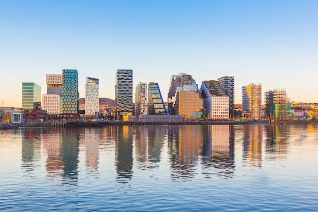 Moderne gebouwen in oslo met hun weerspiegeling in het water