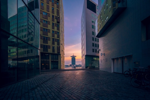 Moderne gebouwen met glazen ramen onder een bewolkte hemel tijdens de zonsondergang in de avond