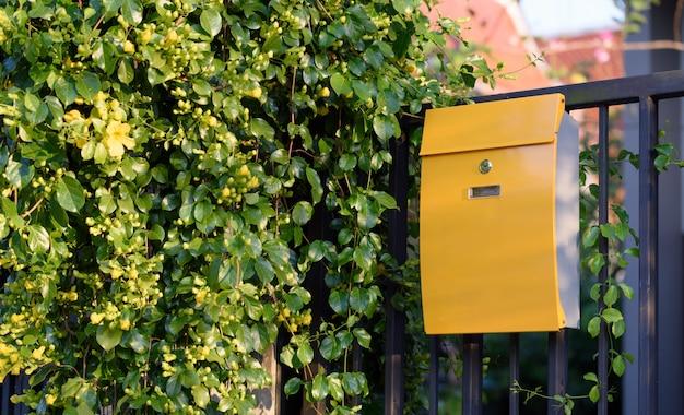 Moderne gele brievenbus op zwarte omheining met mooie geelachtergrond