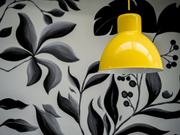 Moderne gele plafondlamp op behang, tropische palmbladeren in zwarte en witte kleuren achtergrond.