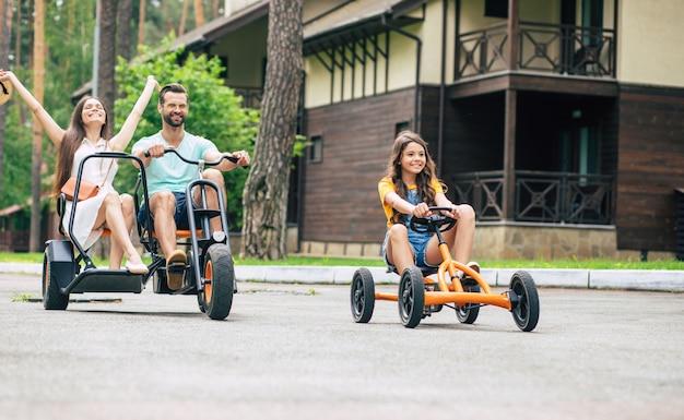 Moderne gelukkige jonge toeristische familie op vakantie rijden op fietsen en samen plezier hebben