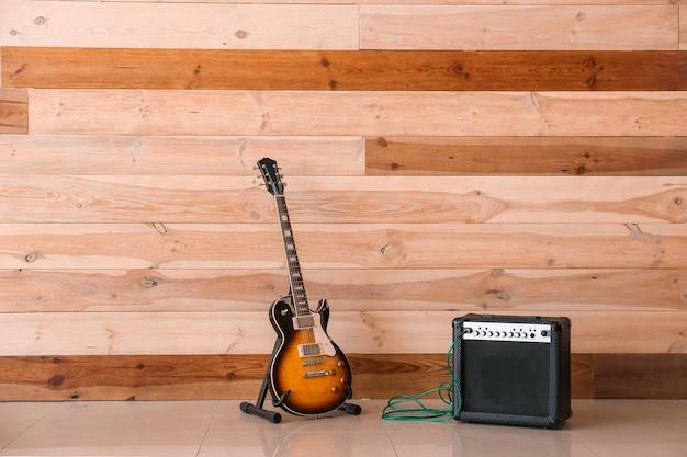 Moderne gitaar en versterker in de buurt van houten muur