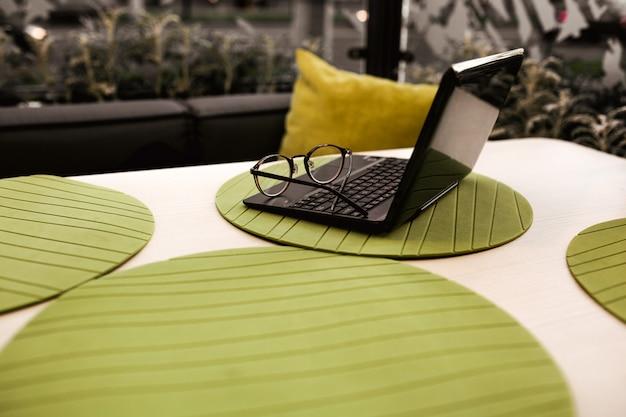 Moderne glazen zakenvrouw liggend op laptop op tafel in café. freelance werken in restaurant.