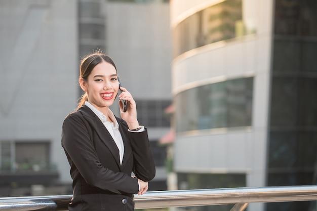 Moderne glimlachende mooie bedrijfsvrouw die slimme telefoon met exemplaarruimte met behulp van