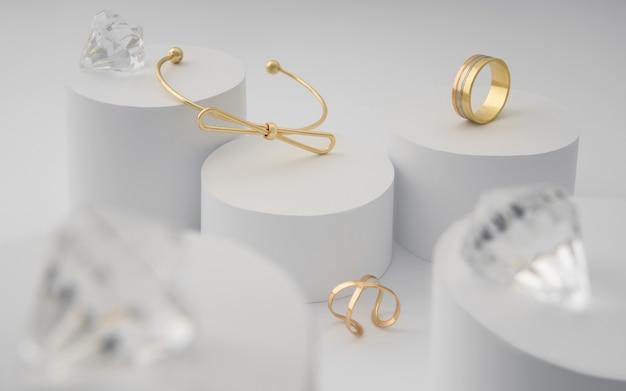 Moderne gouden armband en ringen met briljanten op witte papieren cilinders