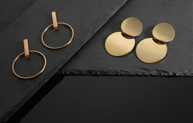 Moderne gouden oorbellen collectie op donkere stenen achtergrond met kopie ruimte