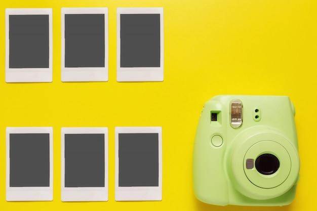 Moderne groene polaroidcamera, foto op gele achtergrond. bovenaanzicht, zachte minimale vlakke stijlsamenstelling. toerisme concept. met kopie ruimte voor tekst