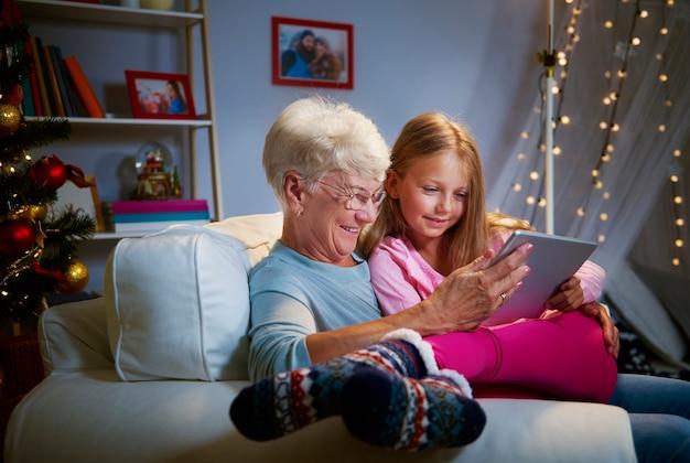 Moderne grootmoeder en kleindochter met behulp van een tablet