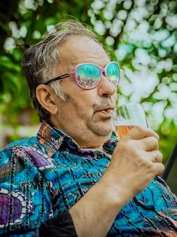 Moderne grootvader drinkt whisky uit een glas