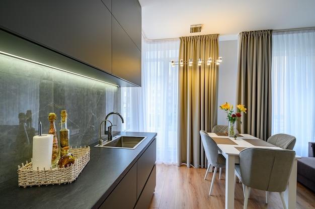 Moderne grote luxe donkergrijze stidio keuken met eetkamer