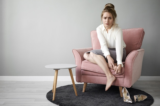 Moderne hardwerkende jonge vrouw die zich moe voelt na een lange wandeling op schoenen met hoge hakken, blootsvoets in een fauteuil zit, haar voeten masseert, pijnlijke gefrustreerde gezichtsuitdrukking heeft. gezondheid en welzijn