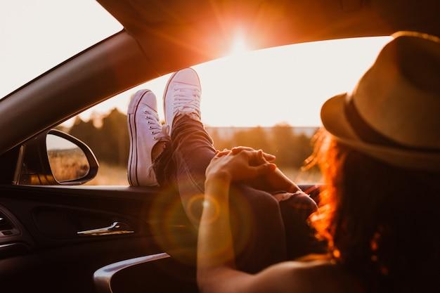 Moderne hipster meisje ontspannen in een auto. voeten buiten het raam bij zonsondergang. reizen concept