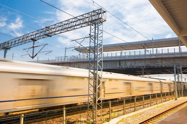 Moderne hogesnelheidstrein bij het station met motieonduidelijk beeldeffect
