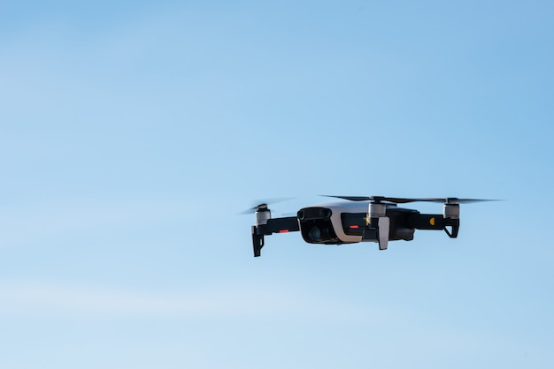 Moderne hommel met camera vliegen op blauwe hemelachtergrond.