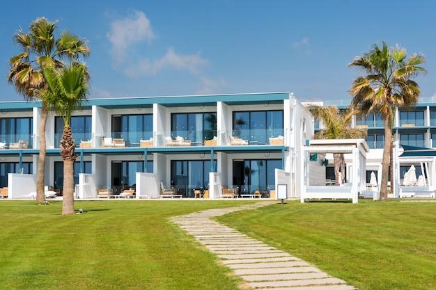 Moderne hotelgebouwen aan de kust met palmbomen en groen gazon