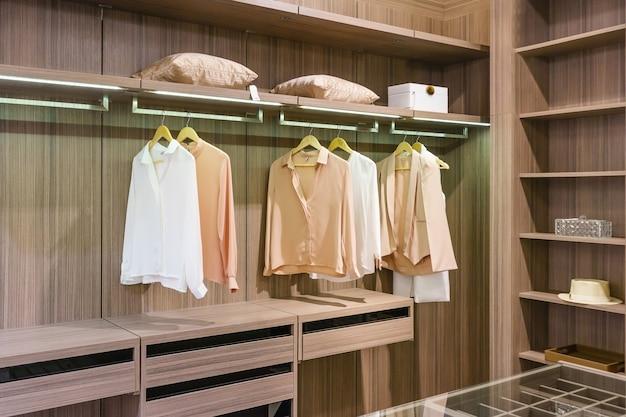 Moderne houten garderobe met kleren die op spoor in gang hangen in kastontwerpbinnenland