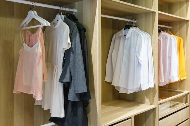 Moderne houten kledingkast met kleding die op spoor in gang hangt in kastontwerpbinnenland