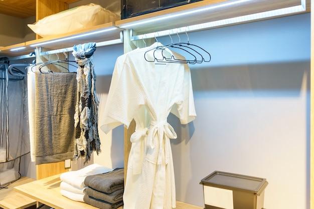 Moderne houten kledingkast met kleren die op spoor in gang in kast hangen
