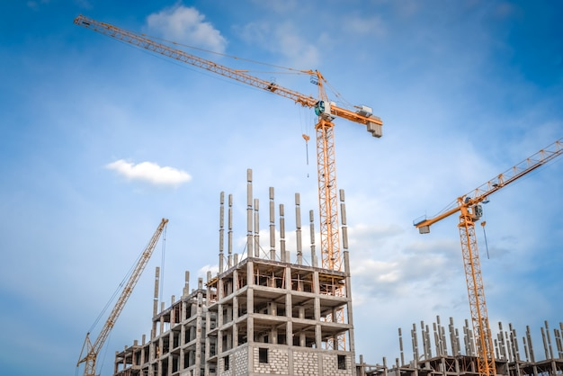Moderne huizen in aanbouw en industriële bouwkranen