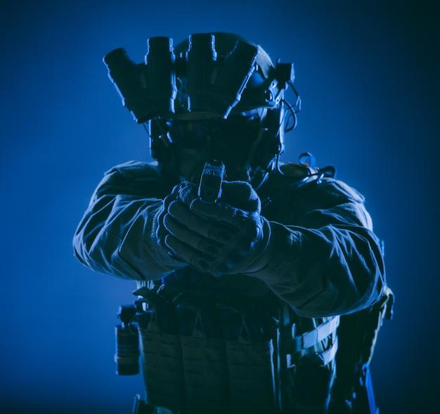 Moderne infanteriesoldaat, special forces-jager, politie swat-officier in helm en kogelvrije vesten, uitgerust nachtzichtapparaat, gericht met servicepistool in de camera, vooraanzicht, low key studio-opname