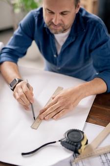 Moderne ingenieur met potlood en liniaal lijn tekenen op blauwdruk zittend aan tafel en werken aan nieuwe schets