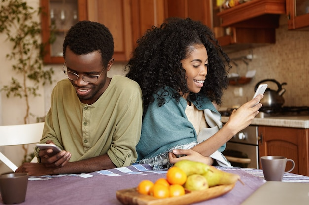 Moderne internet verslaafde jonge afro-amerikaanse echtpaar met behulp van elektronische gadgets tijdens het ontbijt