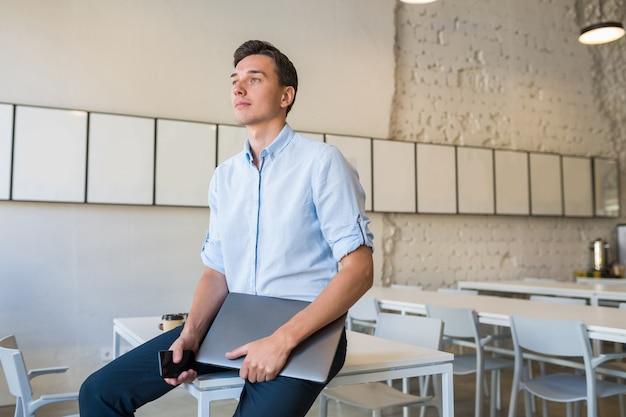 Moderne jonge aantrekkelijke glimlachende man zit in co-working open kantoor, met laptop