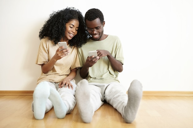 Moderne jonge donkere paar genieten van online communicatie thuis. knappe man in glazen met mobiele telefoon, winkelen via internet