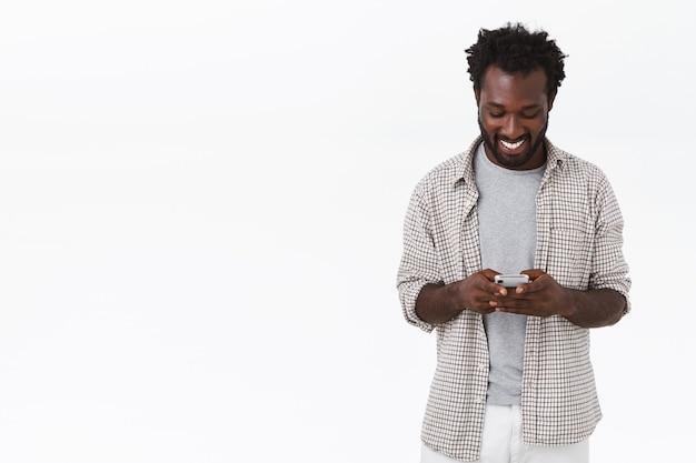 Moderne jonge gelukkige afro-amerikaanse bebaarde man in casual effen shirt