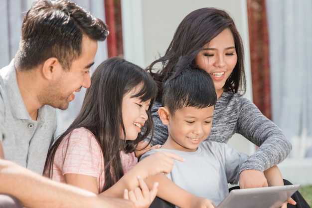 Moderne jonge gezin met behulp van tablet