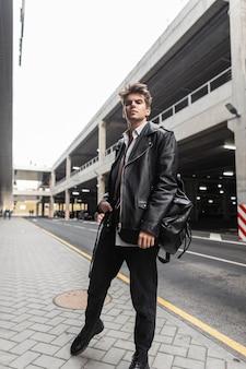 Moderne jonge hipster man in mode zwarte vrijetijdskleding poses in de stad in de buurt van de weg. trendy urban jongensmodel in een stijlvolle leren jas oversized in broek in laarzen loopt buiten. street style.
