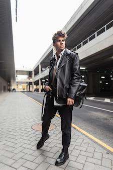 Moderne jonge hipster man in trendy zwarte vrijetijdskleding poses in de stad in de buurt van de weg. stijlvol modern stadsmodel in een stijlvolle leren jas oversized in broek in laarzen buitenshuis. straatmode.