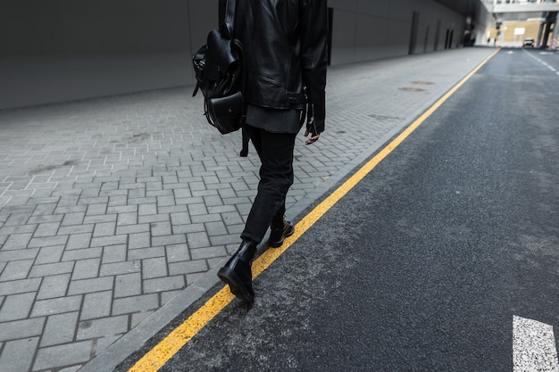Moderne jonge man in een stijlvol jasje in vintage jeans in leren mode-laarzen met een trendy zwarte rugzak loopt buiten op straat. man in jeugd zwarte kleding reist in de stad. gele lijn