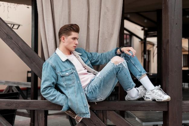 Moderne jonge man in modieuze casual spijkerbroek kleding in stijlvolle sneakers ontspant op houten reling in de stad. aantrekkelijke mode man in vintage jeugd denim slijtage buitenshuis. zomer herenkleding.