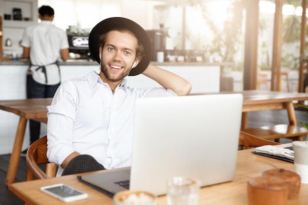 Moderne jonge man in trendy hoofddeksels plezier alleen, genieten van vrije tijd bij coffeeshop, surfen op internet, met behulp van gratis wifi op laptop, luisteren naar muziek online op oortelefoons