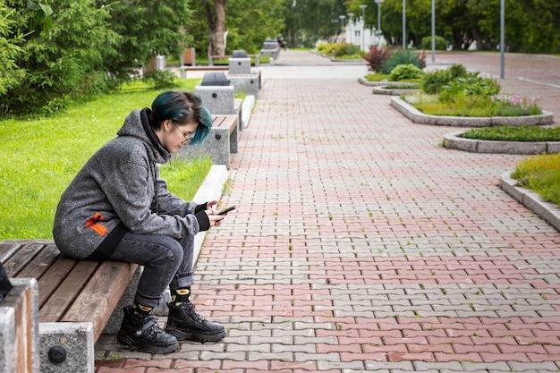 Moderne jonge meisje kijkt naar het scherm van de smartphone op straat onlinecommunicatie
