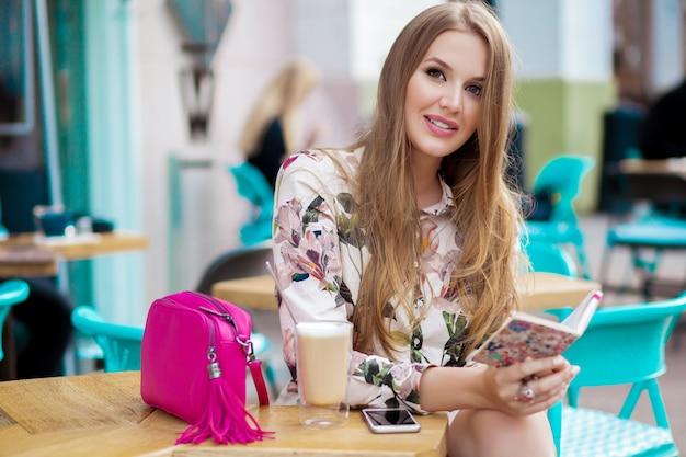 Moderne jonge stijlvolle vrouw zitten in café