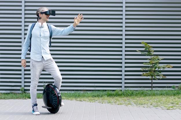 Moderne jonge volwassen mannelijke zakenman student freelancer rijden op ecologische elektrisch vervoer futuristische eco elektrische eenwieler scooter, balancerend elektrisch wiel met virtual reality bril