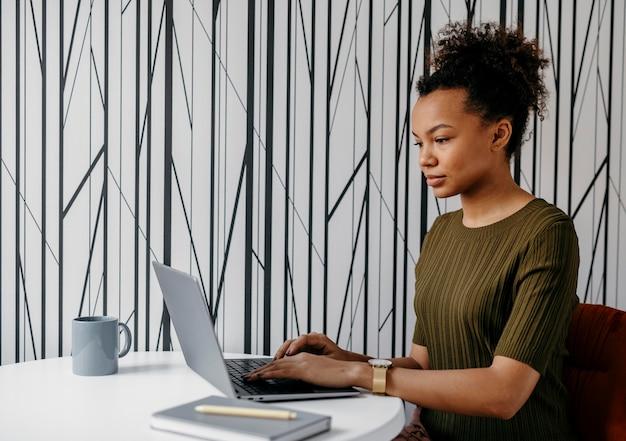 Moderne jonge vrouw die aan haar laptop werkt