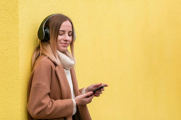 Moderne jonge vrouw die aan muziek op hoofdtelefoons met exemplaarruimte luistert